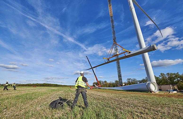 ouvrier levant une pale d'éoliennes